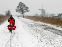 Cycling  0702081019 Kinderdijk. Postwoman. : Countries & Places, Cycling, Nature, People, Profession, Seasons, The Netherlands, Winter, Zuid-Holland